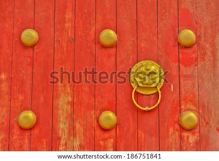 golden lion head on  old chinese traditional door - stock photo