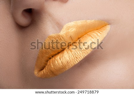 Golden lips. Close up shoot of young beautiful girl with perfect skin: makeup mouth zone. Creative lips with golden lipstick . Stylish lips close up - stock photo
