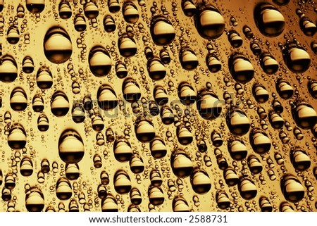 Golden macro photo of water drops on a brilliant surface - stock photo