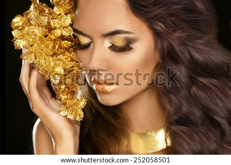 Golden makeup eyes closeup. Beautiful young woman in gold with flowers isolated on black background. Long brown hair.  - stock photo