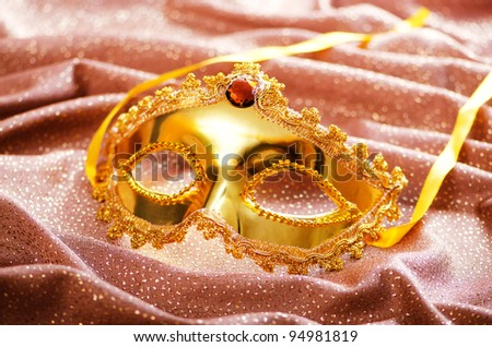 Golden mask on the satin background