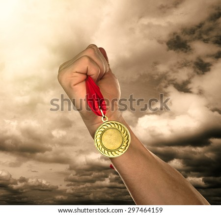 Golden medal in hand on sky background - stock photo