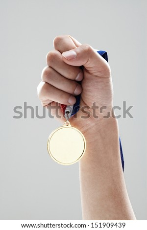 Golden medal in man hand  - stock photo