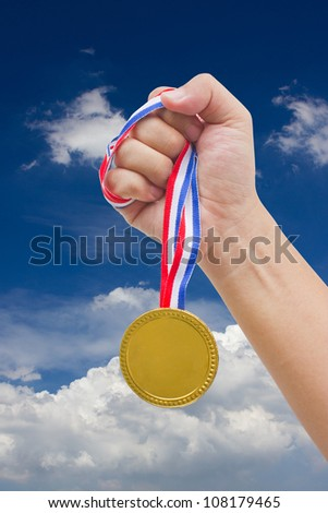 Golden medal in man's hand isolated with blue sky. - stock photo
