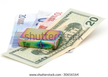 Golden metal cigarette lighter. Euro and dollar banknotes. Selective focus - stock photo