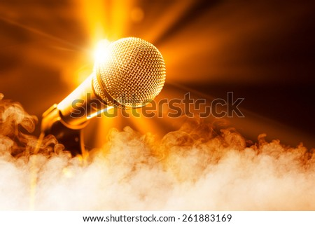 golden microphone on stage with smoke - stock photo