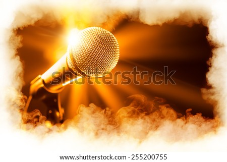 golden microphone on stage with smoke frame - stock photo