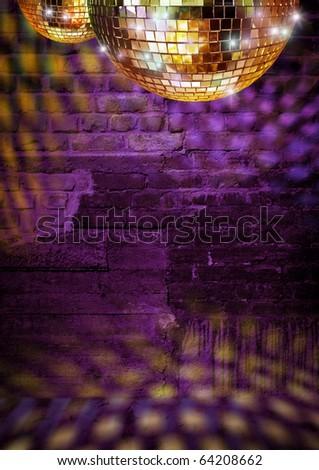 Golden mirror balls reflect lights on dramatic dark disco brick wall - stock photo