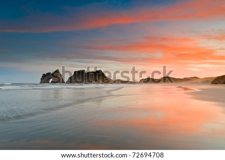 Golden morning at a beach with fiery sunrise - stock photo