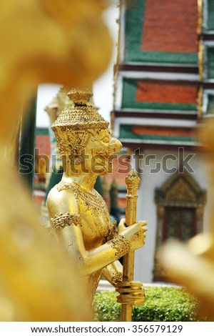 Golden mythical figures at Wat Phra Kaew the Grand Palace, Bangkok, Thailand.           - stock photo