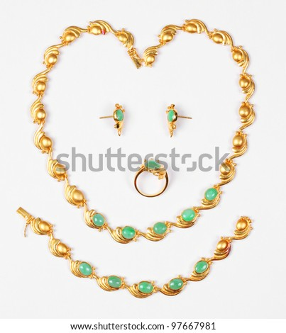 Golden necklace, earrings, ring, bracelet with jade isolated on white background. - stock photo