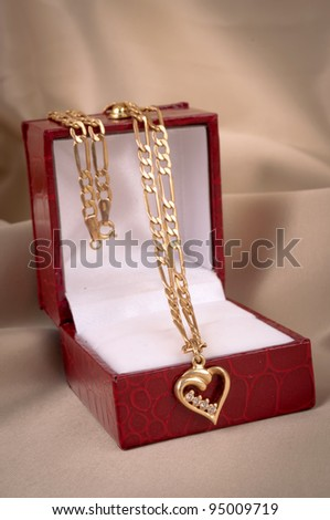 Golden necklace with heart-shape pendant in the box, on the beige silk