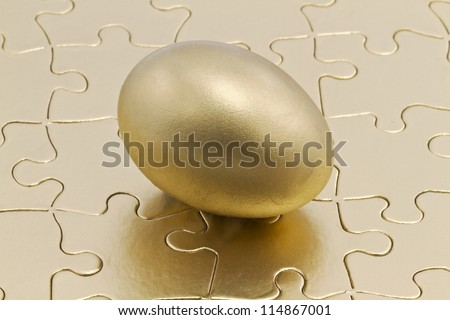 Golden nest eggs sits on metallic gold puzzle; savings is the key to the financial and business puzzle. - stock photo