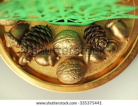 golden nuts, acorns, cones on plate - stock photo
