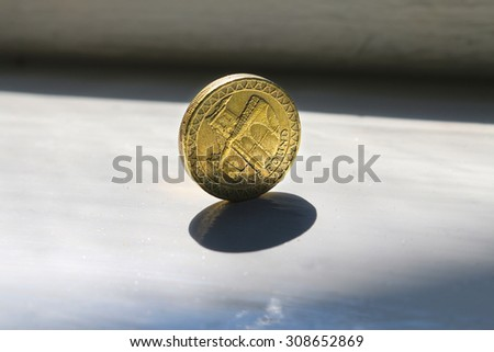 Golden one pound coin with shadow. - stock photo