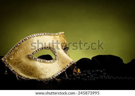 Golden ornate Venice mask and black pearls over green background - stock photo