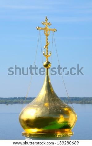 Golden orthodox cross. Church of St John the Baptist in Nizhny Novgorod, Russia on a Volga river. Church was built in the 15th century. - stock photo