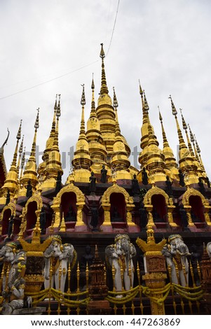 golden pagoda  in temple at Phrae, northern of Thailand, white sky, cloudy   - stock photo