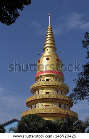 Golden Pagoda. Set in the grounds of the sleeping Buddha temple. The gold spire reflecting the morning sun.