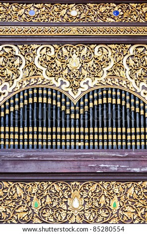 Golden pattern carving in on the window of Thai church. - stock photo