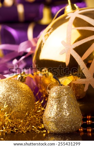golden pear,matte surface gold ball and big gold ball with snowflake, gold tinsel against violet or purple xmas gift boxes  - stock photo
