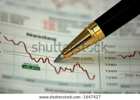 Golden pen showing curves on financial report/magazine