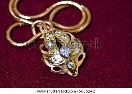 Golden pendant with chain on velvet background. - stock photo