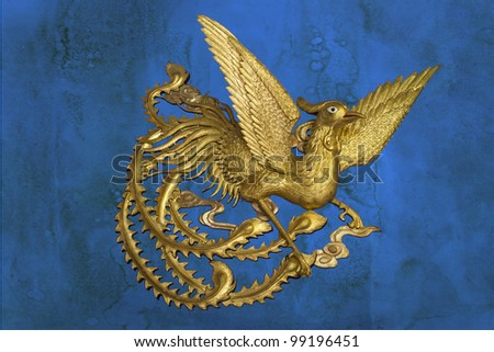 golden phoenix on blue stain wall background - stock photo