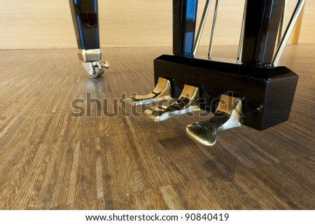 golden piano pedals of a concert grand piano standing on concert stage - stock photo