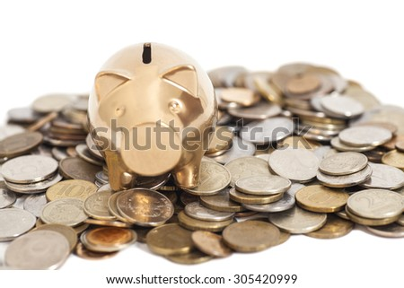 Golden piggy bank on coins isolated on white