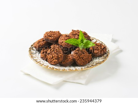 golden plate with portion of chocolate cookies dipped in dark chocolate - stock photo