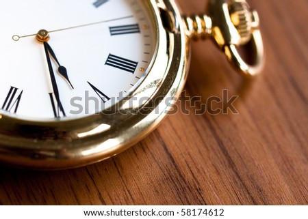 Golden pocket watch on a wooden surface (close-up) - stock photo