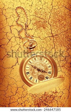 Golden pocket watch with chain on cracked background - stock photo