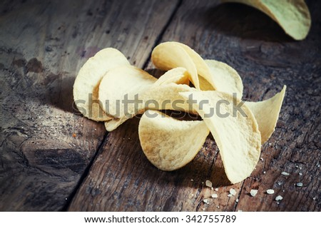 Golden potato chips and sea salt on the old wooden background, toned image, selective focus - stock photo