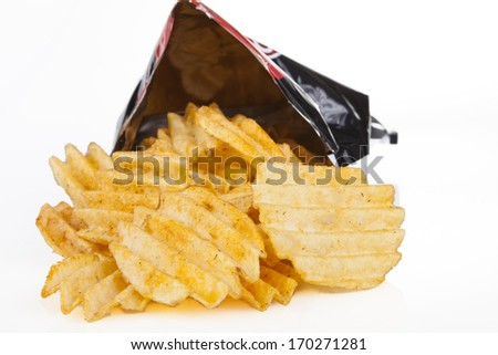 Golden potato chips pouring out os a bag on white background - stock photo