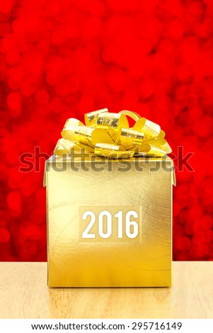 Golden Present box with 2016 year word at red bokeh light background, Leave space for adding your text. - stock photo