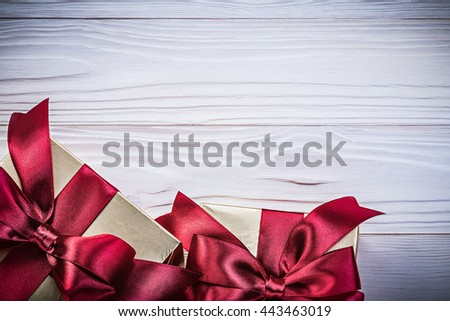 Golden present boxes on wood board directly above holidays concept. - stock photo
