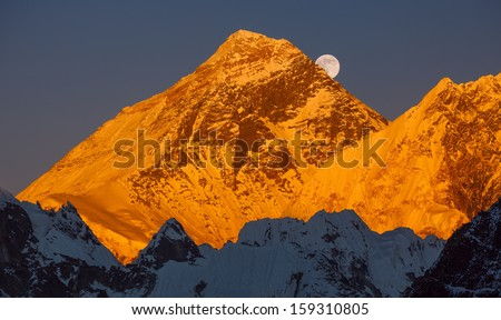 Golden pyramid of Mount Everest (8848 m) at sunset. Ascending moon. Canon 5D Mk II. - stock photo