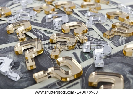 Golden question marks made of plexiglas lie on dollar background/Dollar background with question marks - stock photo
