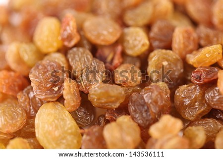 Golden raisins are located a whole background. - stock photo