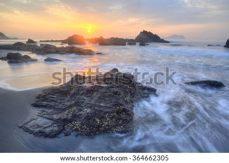 Golden rays of rising sun light up the beautiful rocky beach of Yilan Coast near Taipei, Taiwan ~ A fascinating sunrise scenery at Yilan seashore under dramatic dawning sky (Long Exposure) - stock photo