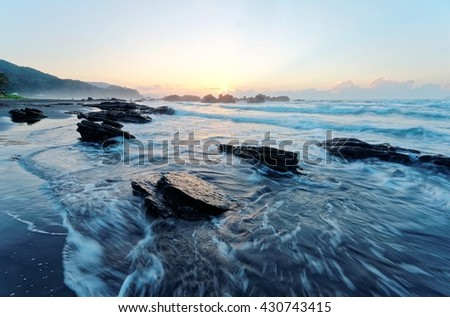 Golden rays of the rising sun light up the waves at rocky Wai'ao Beach in Ilan, Taiwan ~ A beautiful beach illuminated by the first ray of morning sunshine at Wai'ao, Taiwan ( Long Exposure Effect )  - stock photo