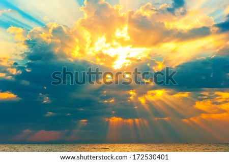 golden rays of the sun breaking through the storm clouds - stock photo