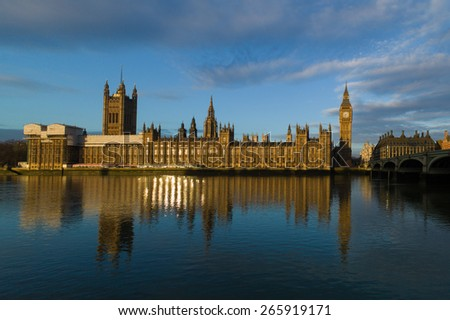 Golden reflections of the rising sun caught in the windows of the Houses of Parliament, Westminster, London - stock photo