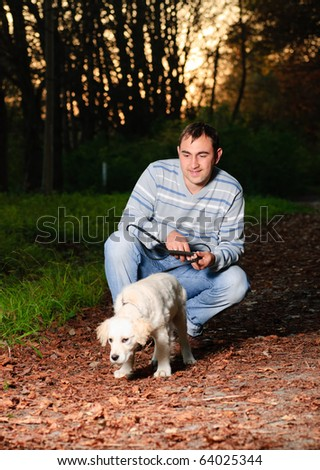 Golden retriever and man are playing in park - stock photo