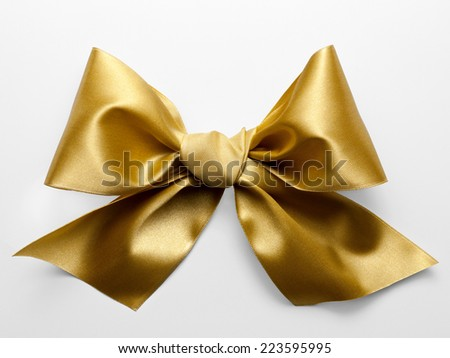 Golden ribbon bow with real shadow on white background - stock photo