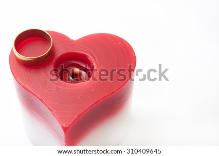 Golden ring and candle in the heart shape on the white background. - stock photo
