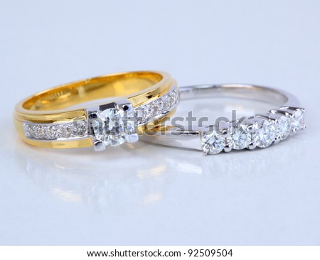 Golden ring with diamond and contemporary diamond ring, isolated on white background. - stock photo
