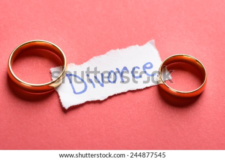 Golden Rings On Torn Piece Of Paper With Divorce Text - stock photo