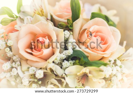 golden rings on wedding bridal bouquet with white, peach and orange roses. Wedding theme - stock photo